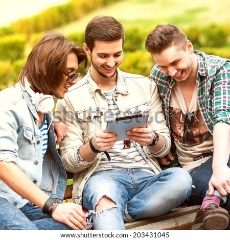 Three young men friends using tablet computer in park