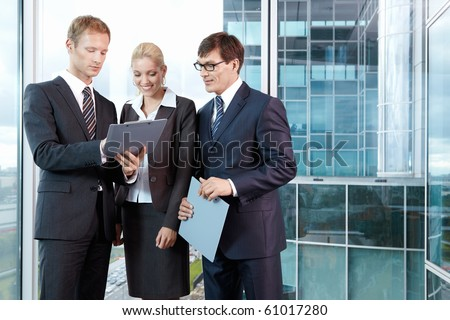 Three young men in business suits in the office