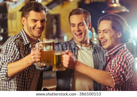Three young men in casual clothes are smiling and clanging glasses of beer together while standing near bar counter in pub