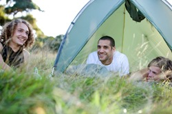 Three young men laying in the grass camping