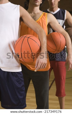 Three young men standing in a court and holding basketballs