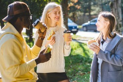Three young multiethnic hungry people students discussing, having lunch, and eating to-go food while standing up outdoor in sunny autumn day. Making friends, get-together meeting concept.