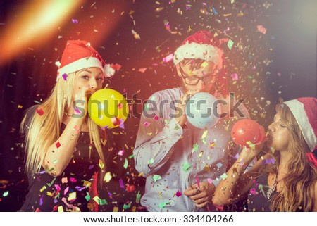 Three young people at New Year's Eve party on midnight blowing colorful balloons and having fun #334404266