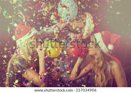 Three young people at New Year\'s Eve party on midnight blowing colorful balloons and having fun
