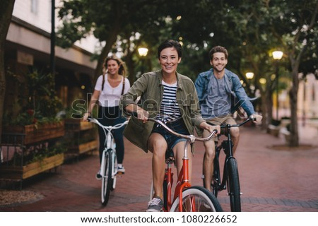 Photo of  Three young people cycling down the street. Male and female friends on road with their bikes.
