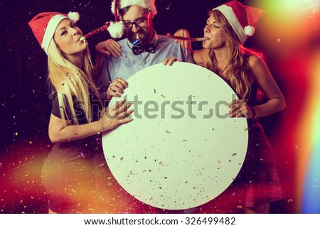 Three young people, having fun at New Year's Eve Party, blowing whistles and holding cardboard blank circle. stock photo