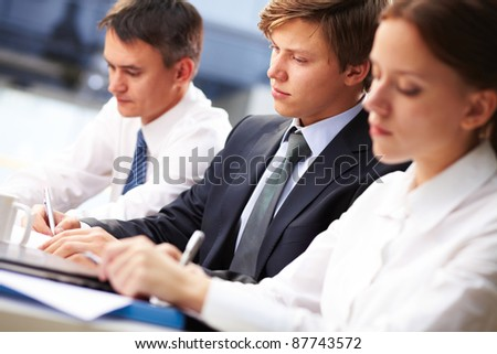 Three young people making notes at lecture with focus on serious student
