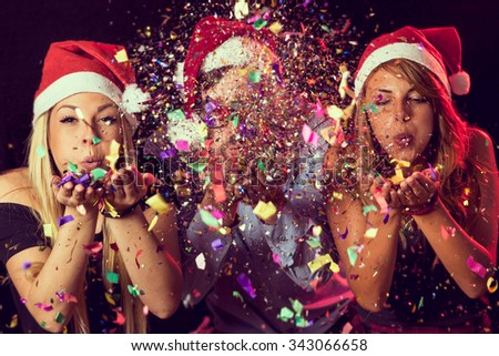 Three young people wearing Santa's hats, blowing colorful confetti at midnight at New Year's Eve party #343066658