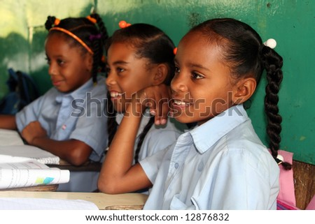 Three young schoolgirls sitting next together in the classroom - stock photo