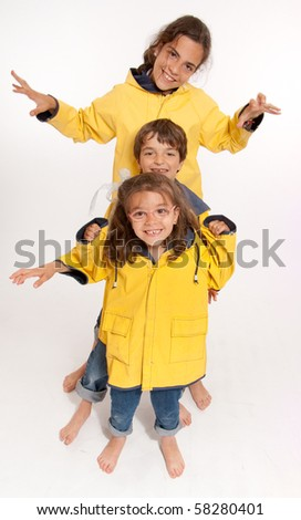 Three young siblings barefoot wearing jeans and yellow raincoats #58280401
