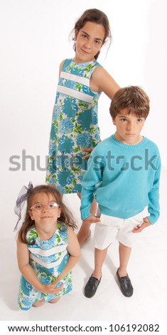 Three young siblings dressed in matching clothes