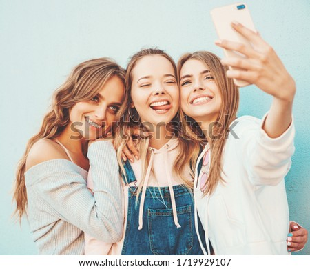 Three young smiling hipster women in summer clothes.Girls taking selfie self portrait photos on smartphone.Models posing in the street near wall.Female showing positive face emotions.Showing tongue ストックフォト ©