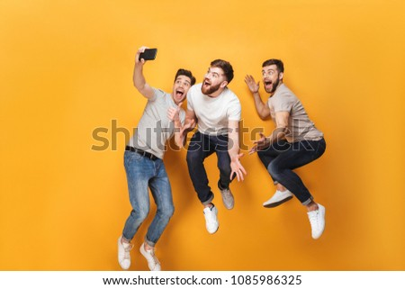 Three young smiling men taking a selfie together while jumping isolated over yellow background #1085986325