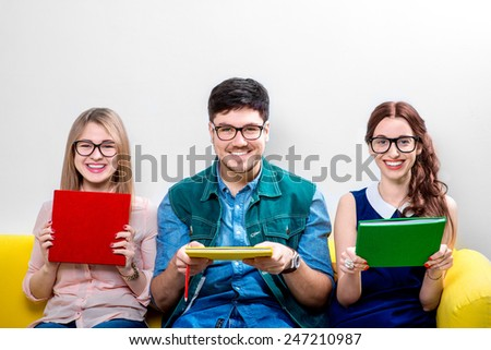 Three young students or nerds holding colorful books and sitting on the yellow couch