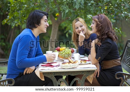 Three young students sitting at an outdoor restaurant table enjoying a cup of coffee and fruit while chatting