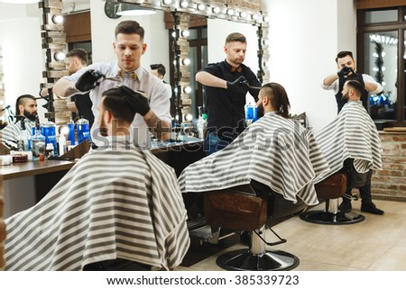 Three young stylish men with dark hair sitting in barber shop and doing haircuts, barbers in black gloves.