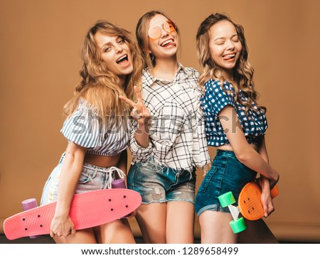Three young stylish smiling beautiful girls with colorful penny skateboards. Woman in summer hipster checkered shirt clothes posing on golden background.Positive models having fun and going crazy #1289658499