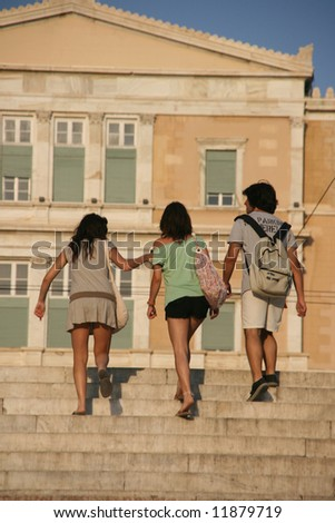 three young teens walking in athens with greek parliament blur in background