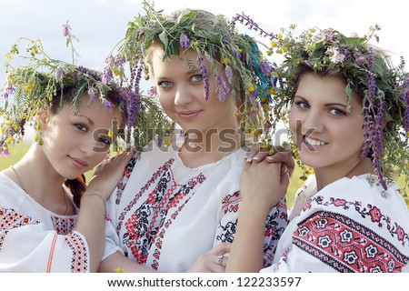 three young Ukrainian girls among the nature with smiles on faces in beautiful Ukrainian suits