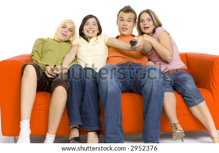 Three young woman and a man are sitting on the orange couch and looks like watching TV. Man is holding remote control. The're looks terrified.