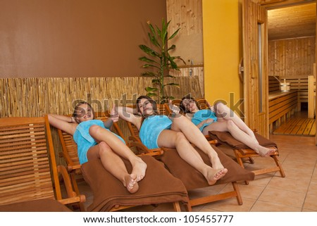 three young woman lying on loungers in front of a sauna and posing with the thumbs up sign