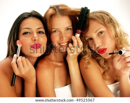 Three young women applying makeup mirror.