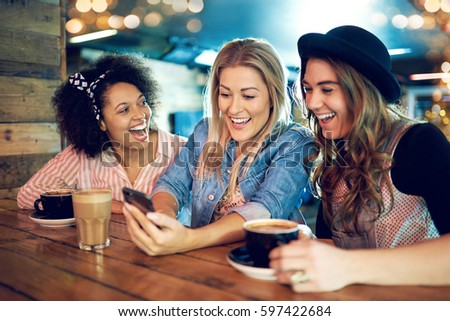 Three young women at wooden table in cafe laughing, looking at smartphone, when girl in blue denim showing something on the screen to her friends #597422684