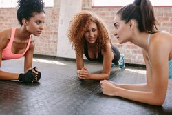 Three young women doing pushups together in gym. Group of female working out in healthclub.