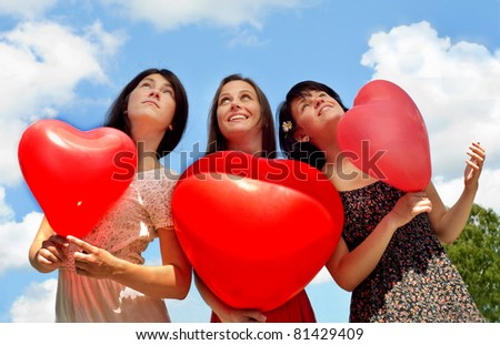 Three young women holding red balloons against sky