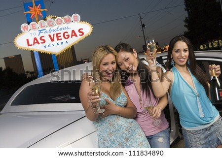 Three young women in front of a 'Welcome to Las Vegas' sign