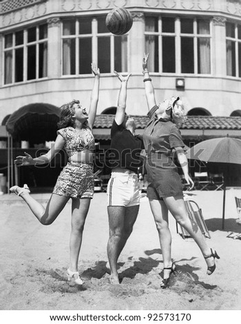 Three young women playing with a ball on the beach
