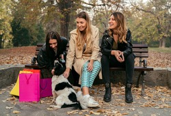Three young women resting in park bench after day spent in shopping and petting dog