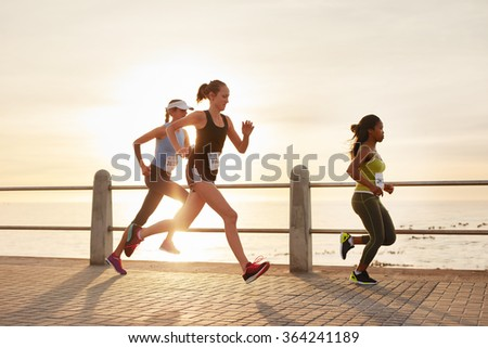 Three young women running on a road by the sea. Group of divers runners training on seaside promenade during sunset.