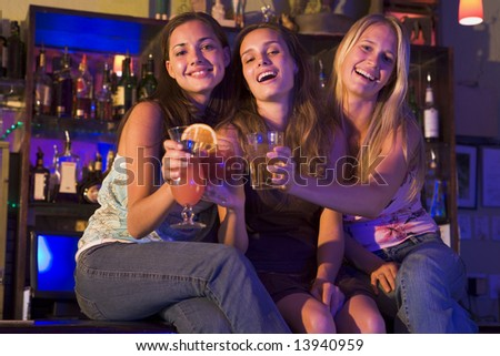 Three young women sitting on a bar counter, toasting the camera - stock photo