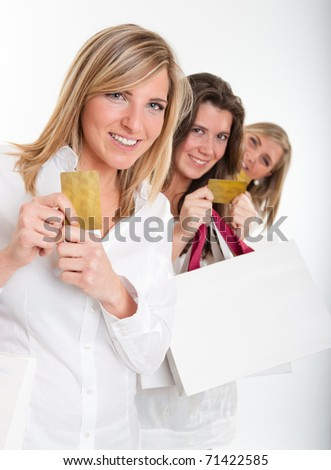 Three young women with happy expressions with credit cards holding lots of shopping bags