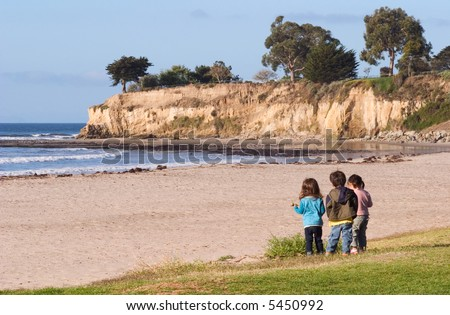Three youngsters looking at the Pacific coastline and tide-pools in Santa Barbara, California.