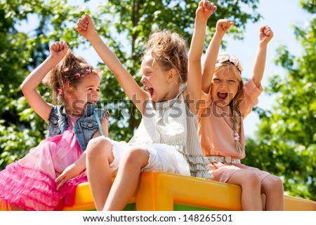 Threesome girl friends raising hands together and shouting in park.