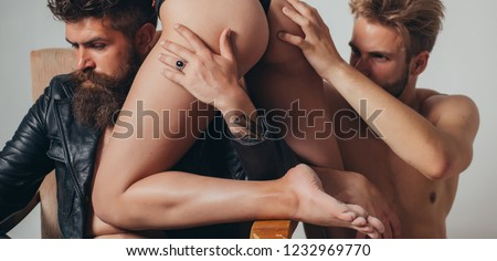 Threesome group sex game. Dominantning in the foreplay sexual game. Froup playing domination games. Sexy evening for young couple and sex protection. Safety sex concept #1232969770