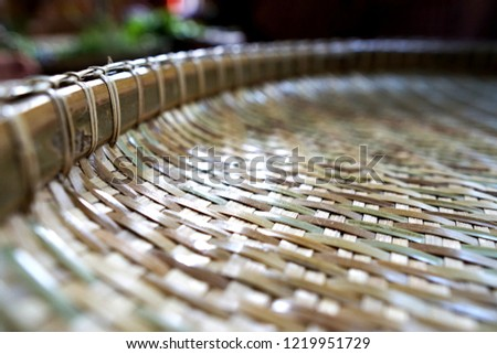 Threshing basket rice-winnowing basket large,round bamboo tray Close up thai threshing basket texture background.Weaving material for dry food,texture background empty basket Thailand selective focus
