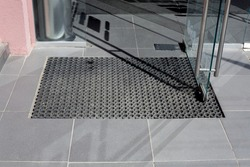 threshold made of gray ceramic tiles at entrance to store with a rubber foot mat and open glass door with metal handle at office building close-up front view, nobody.