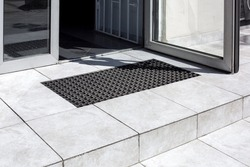 threshold made of light gray ceramic tiles with steps at the entrance to the store with a foot mat and an open glass door at the facade of an office building close-up, nobody.
