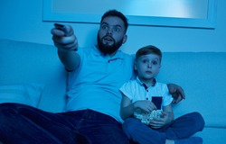 Thrilled adult bearded dad with controller in hand and little son with popcorn sitting on sofa and watching TV together at night time at home