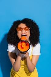 thrilled african american woman in orange eyeglasses screaming in megaphone on blue