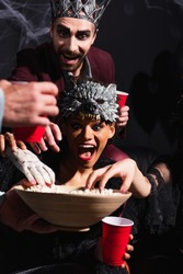 thrilled african american woman in wolf mask taking popcorn with creepy toy hand near friends on black