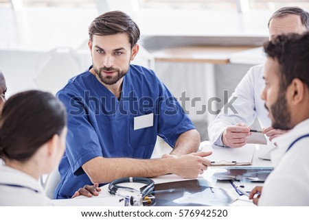Thrilled doctor arguing with associates during meeting #576942520