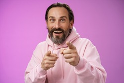 Thrilled energized charismatic happy lucky adult handsome bearded man pointing camera smiling widen eyes gazing impressed see famous person express amazement joy, purple background