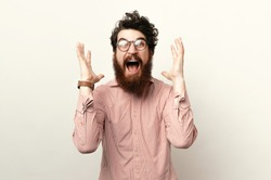 Thrilled excited attractive bearded man in glasses screaming and gesturing with raised palms
