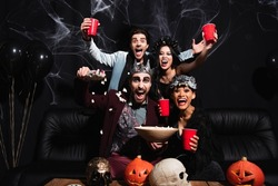 thrilled multicultural friends in halloween costumes near popcorn, carved pumpkins and skulls on black