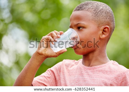 Thristy african boy drinks water from plastic cup
