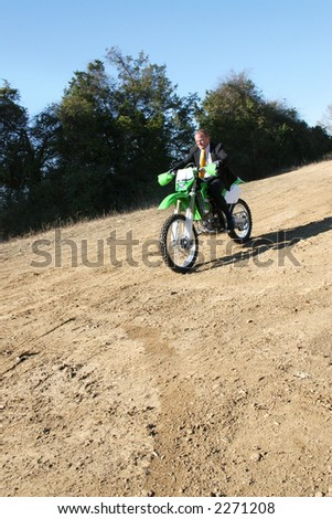 Thrity something business man in suit riding dirt bike on dirt riding track.